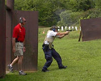 Student fires a gun while instructor watches from behind